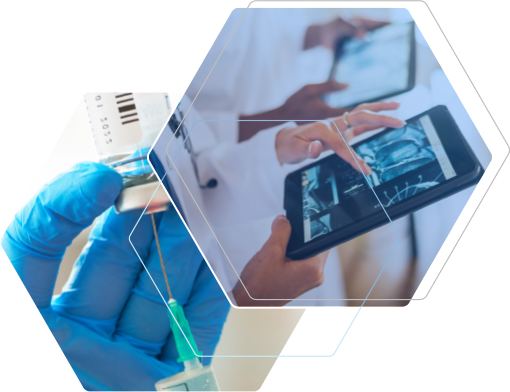 A woman wearing a lab coat and protective gear examines the contents of two vials and two medical professionals reviewing data on tablets